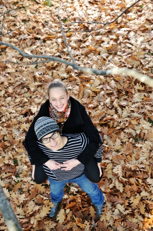 coutryside: Romantic Teenage Couple By Tree In Autumn Park Stock Photo