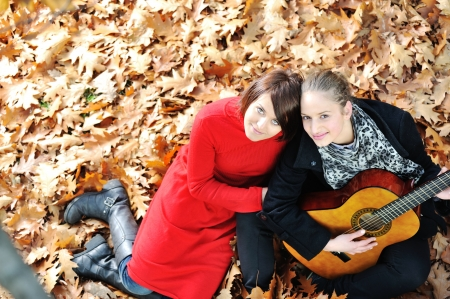 woman guitar: Two girls playing guitar and having good time in nature