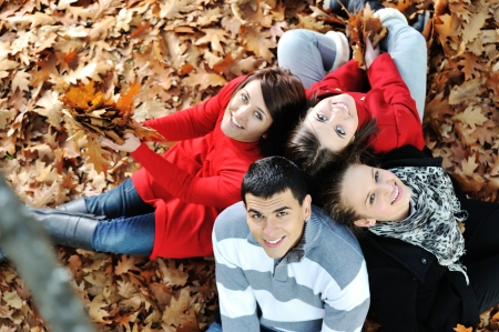 Happy group of young friends together in fall park photo