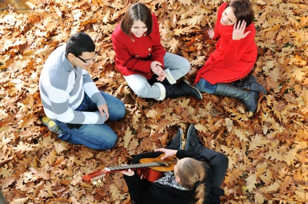sitting on the ground: Teenagers friends playing the guitar at autumn park