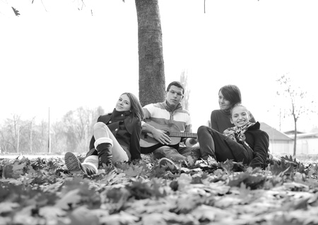 Teenagers friends playing the guitar at autumn park photo