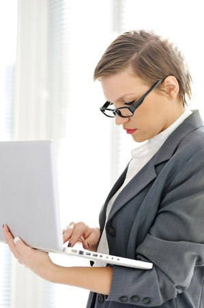 Young business woman at office with laptop Stock Photo - 18476072