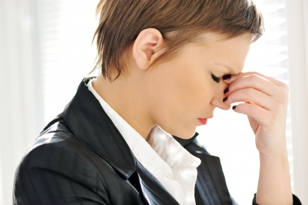 eyestrain: Young depresses stressed business woman at office
