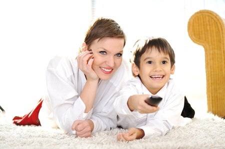 Mom with son lying on floor and watching tv using remote control photo