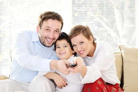 tv home: Family sitting in living room with remote control