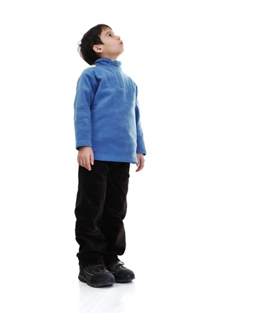 niño parado: Niño pequeño aislado en blanco mirando hacia arriba
