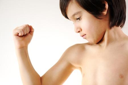 niño sin camisa: Niño que muestra los músculos de sus brazos delgados