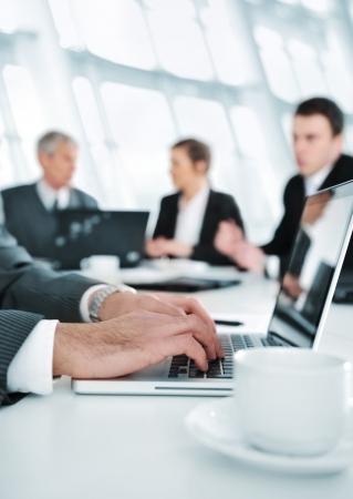 informe comercial: Ambiente de negocios, trabajando en la computadora port?til durante la reuni?n