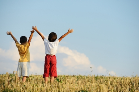 arms in air: Two kids standing on meadow with arms up in air