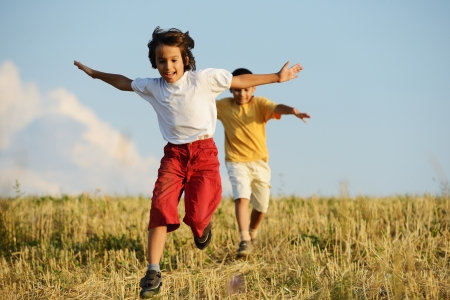Happy children running on beautiful field photo