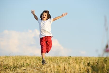 Enfant heureux fonctionnant sur beau terrain Banque d'images