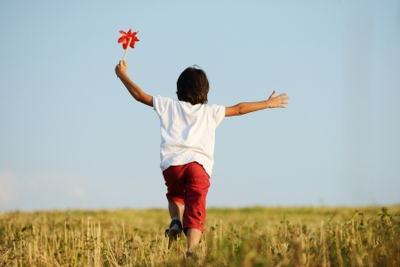 Happy kid running on beautiful field photo