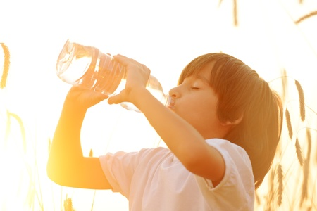 Kid drinking pure fresh water in nature photo