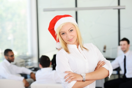Santa girl businesswoman at office with colleagues photo