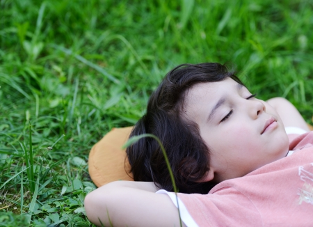 sleeping kid: Closeup portrait of a little happy boy sleeping on grass in nature and dreaming