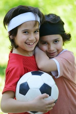Young boys holding football outside photo