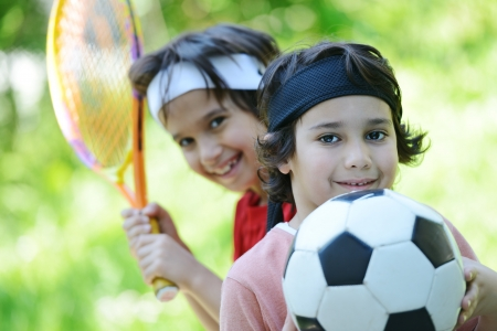 Young boys with football and tennis outside