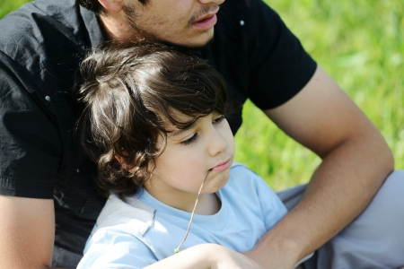 Father and son in nature sitting together photo