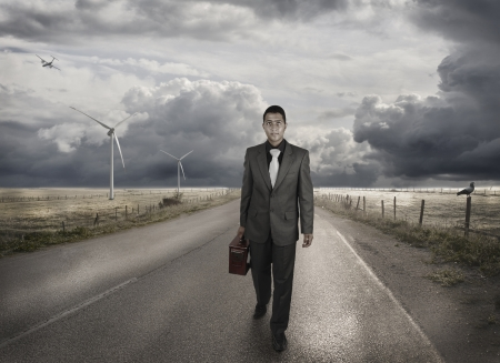 lonely road: A young businessman walking on the road Stock Photo