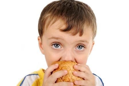 Closeup image of a cute kid eating sandwich photo