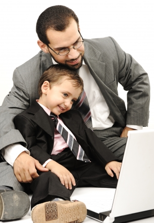 school work: Portrait of a happy young man and his son working on laptop