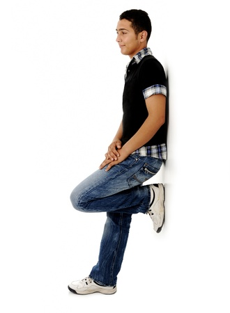standing against: Trendy guy standing agaisnt the wall and smiling Stock Photo