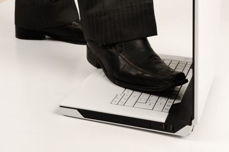 destroying: Business foot walk over laptop with white background Stock Photo