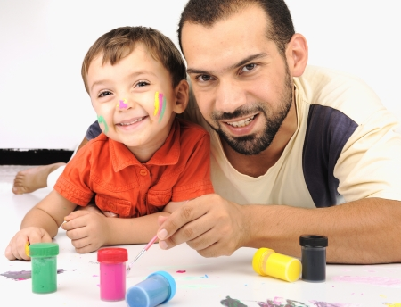 Father and kid playing with paint colors photo