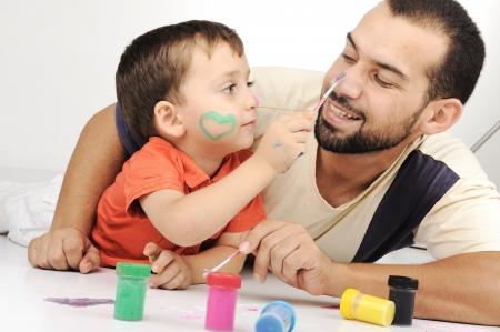 muslim baby: Father and kid playing with paint colors Stock Photo