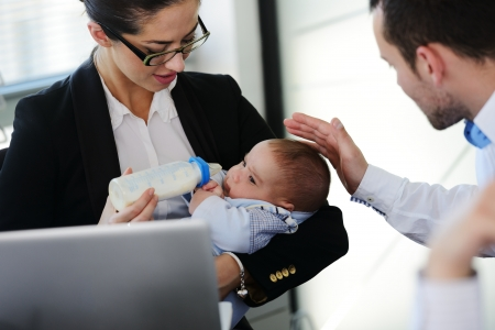 mother helping baby: Business people taking care of baby in office