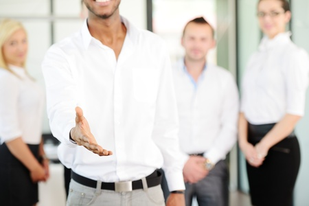 Business person offering you handshake with colleagues in background photo