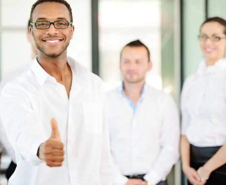 Business person giving you thumb up with colleagues in background photo