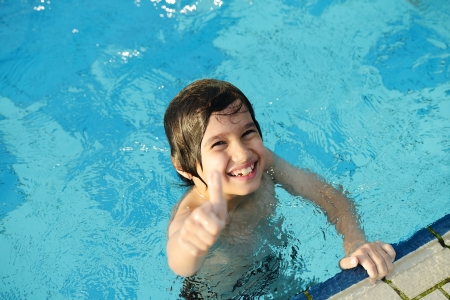 Little happy boy on pool with thumb up photo