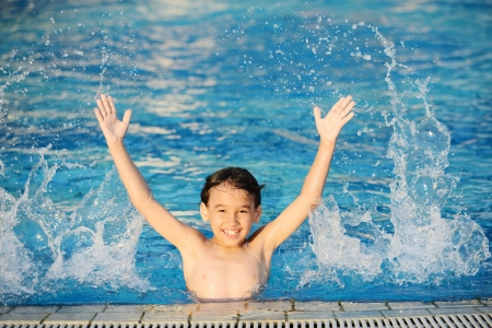 Kid splashing on summer pool Stock Photo