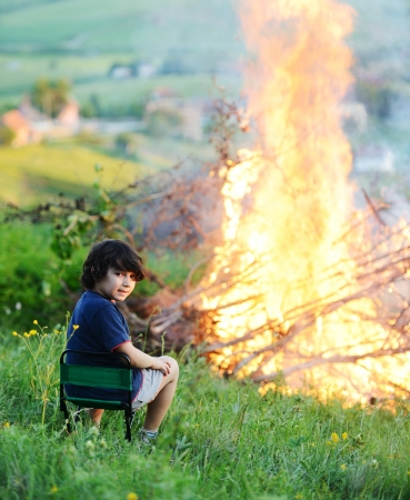outdoor fireplace: Kid beside the big fire Stock Photo