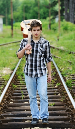 country music: Handsome guy with guitar on a railroad
