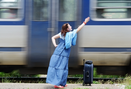 Young woman waving at train photo