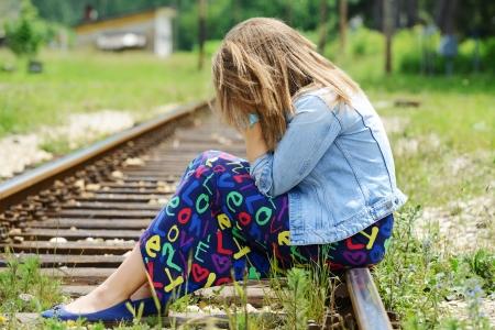 clothes rail: Woman sitting on railway tracks Stock Photo