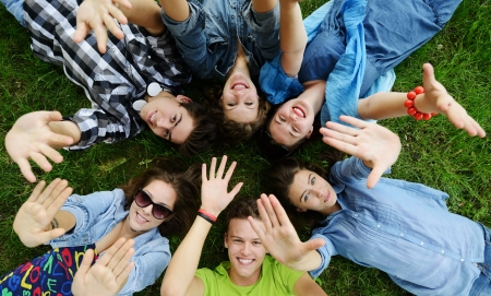 students fun: Group of friends lying on meadow