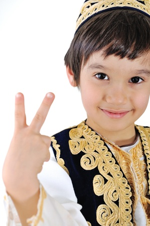 cultural diversity: Little kid in middle-eastern clothes making peace gesture