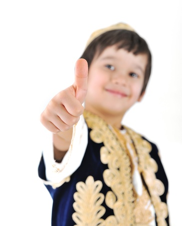 Little kid wearing european traditional clothes with thumbs up photo