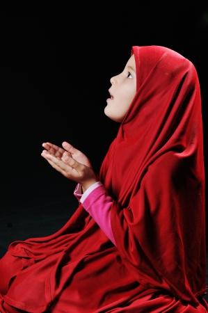 arab teen: Beautiful young muslim girl praying on black background