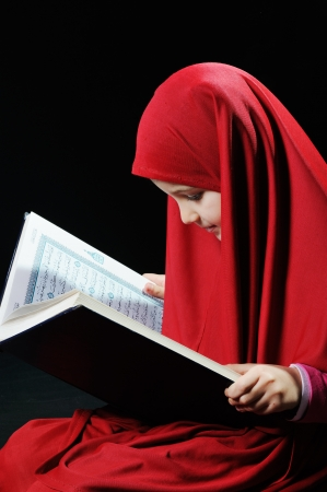 Young muslim girl reading holy koran photo