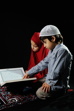 petite fille musulmane: Enfants musulmans de lecture Coran sur fond noir Banque d'images