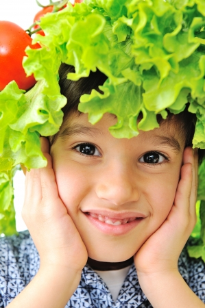 Closeup image of a little kid with tomato and salad hat on his head Stock Photo - 19277424