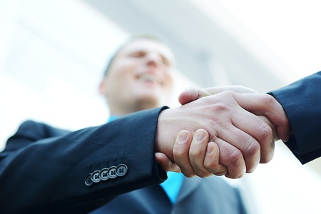 Business třást ruce před moderní budovy s kopií prostoru (selektivní focus)