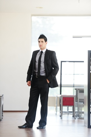 office environment: Attractive young businessman standing in office alone