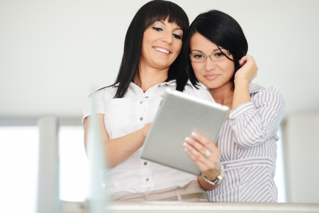 Two businesswomen working on tablet gadget with copy space photo