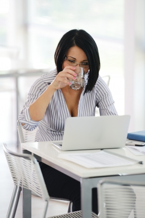 Portrait of a pretty businesswoman sitting at her desk with a laptop looking happy photo