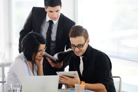 people working together: Three business people working at office with paperwork using tablet and laptop Stock Photo